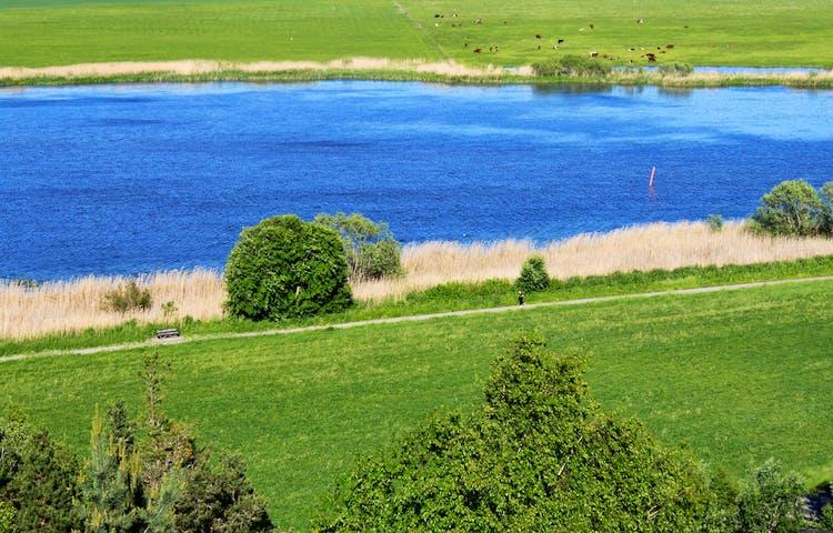 Från en höjd har man utsikt över Fyrisån och gröna ängar runtom. En gångväg löper längs med ån.