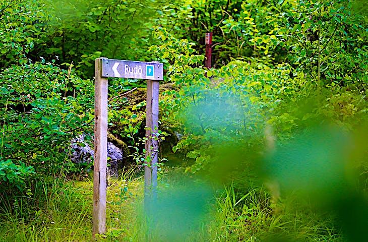 Träskylt bland träd och buskar visar vägen mot Rudö.