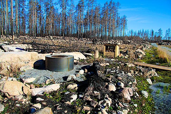 Rastplats med eldstad och vedförråd. Stora stenar blir naturliga sittplatser.
