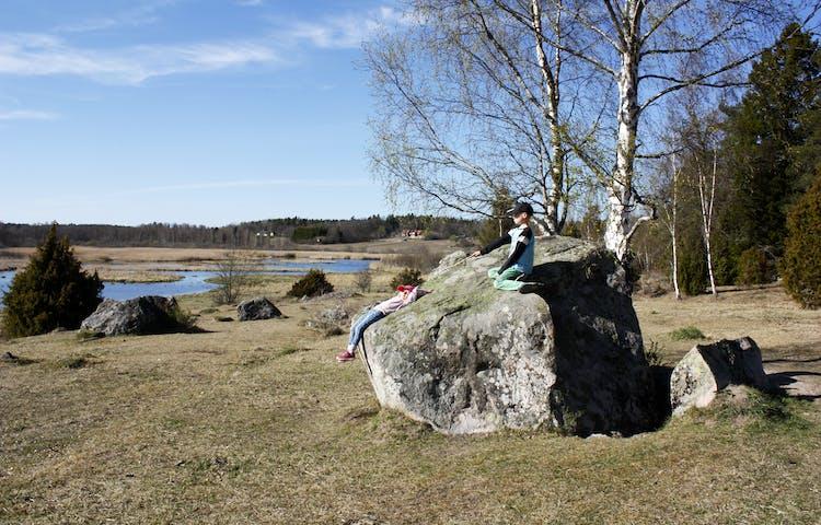 Två barn sitter på ett klippblock. Hagmark leder ned till en våtmark.