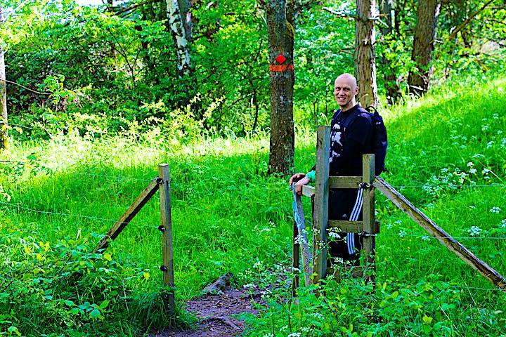 En man öppnar en grind och är på väg att gå in i en hage.