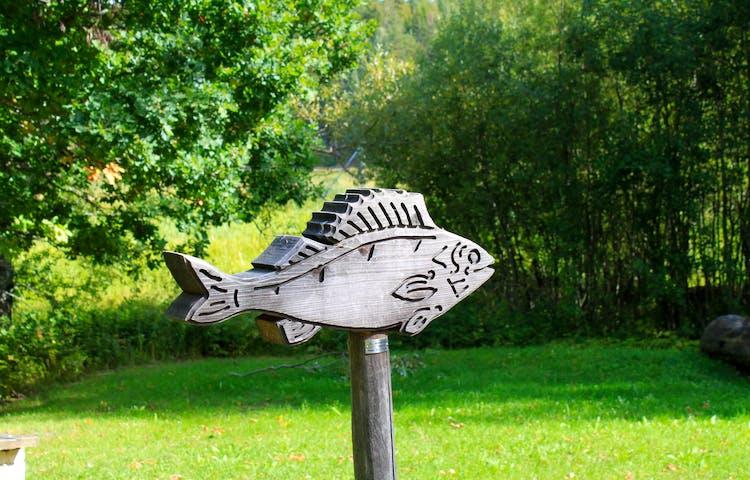 På en plan gräsyta står en trästolpe med en träskulptur av en fisk monterad på toppen. Runtomkring finns många träd.