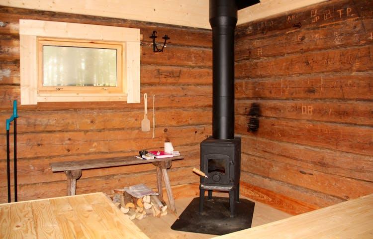 Inne i stugan. Inne i stugan: liten kamin hörnet och väggar i stockvirke.