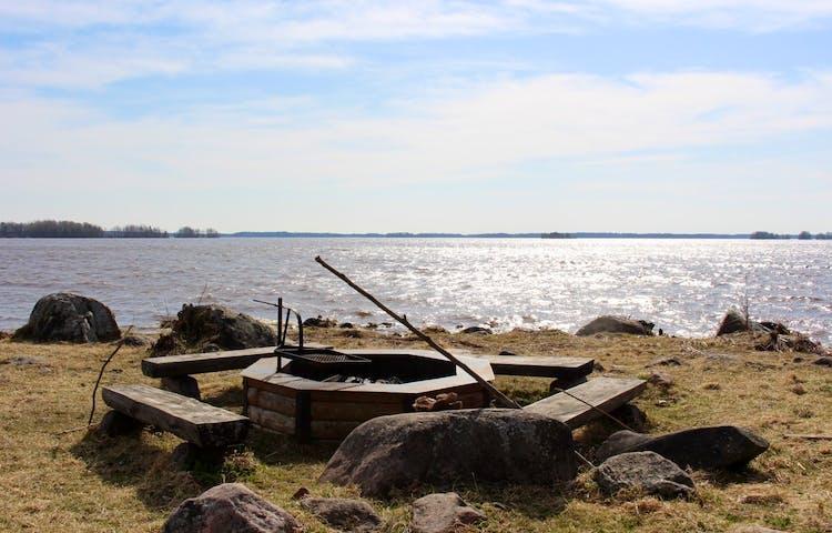 En låg grillplats med fyra sittbänkar omkring står vid havet. Grillplatsen står på gräs och runtom ligger flera stora stenar.