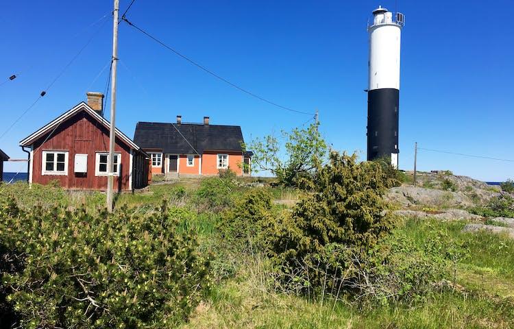 På en ö med ojämn mark och stenhällar står en fyr med två äldre hus vid ena sidan. En hög stolpe med flera elkablar fästa på sig står i närheten av husen.