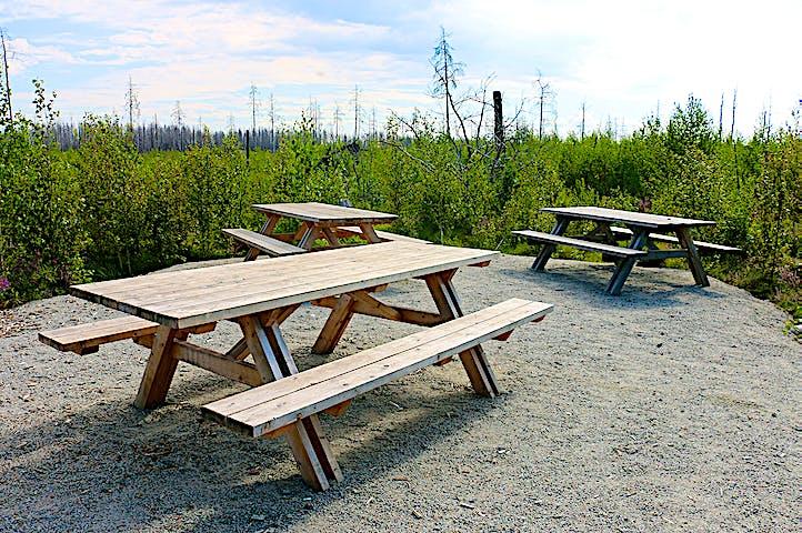Tre picknickbord i trä på en grusplan.