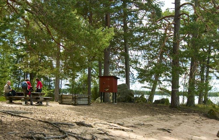 På en sluttande sandstrand står en låg grillplats och ett bänkbord. Vid bänkbordet packar tre vuxna ihop sina ryggsäckar.