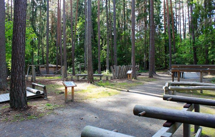 På en plan yta i en skogsglänta står en träningsbana uppställd. Det finns flera olika slags stationer och vid varje station står en informationsskylt.