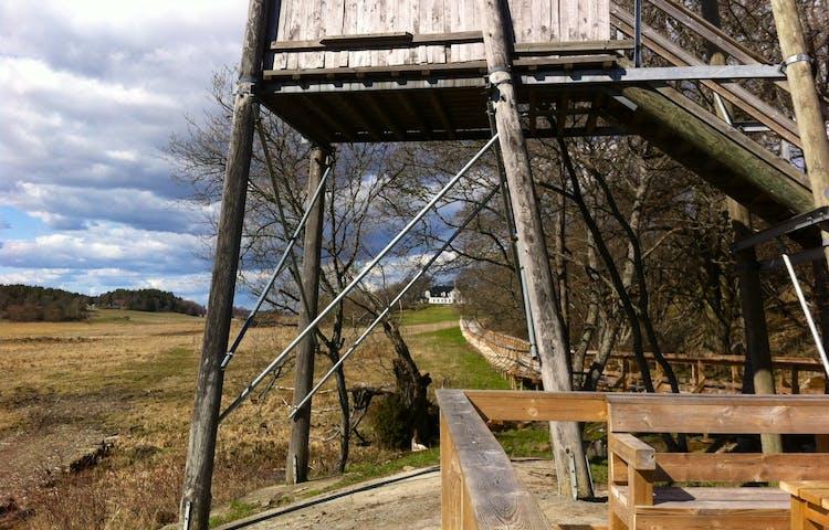 Bild från en plattform. I förgrunden står ett högt fågeltorn och i bakgrunden ligger herrgården.