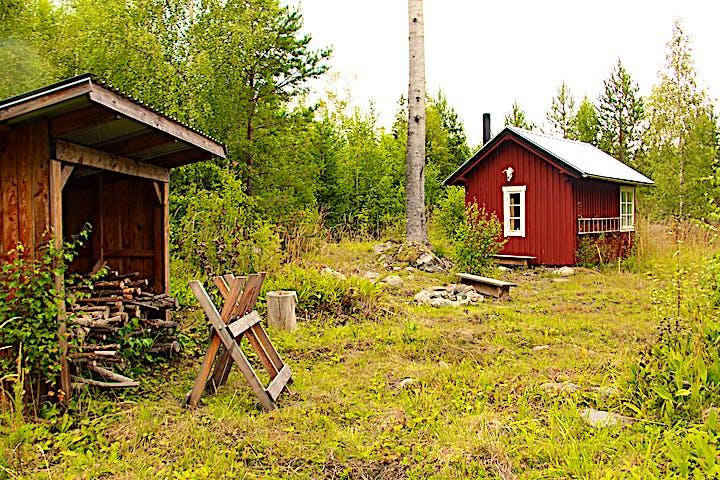 Vedskjul, eldstad och liten röd stuga