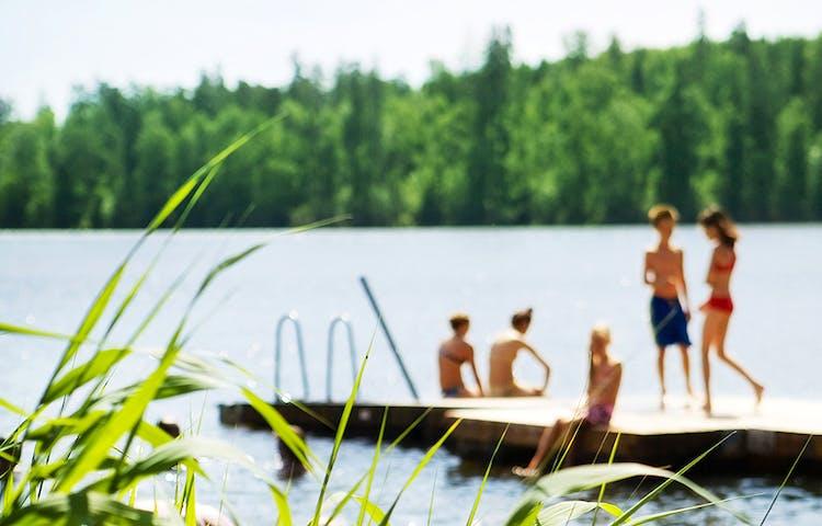 Barn på en badbrygga vid en sjö.