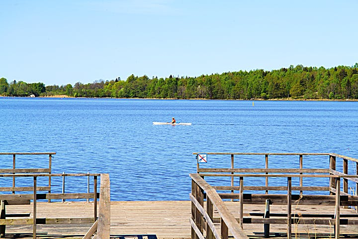 Brygga med träräcke och en skylt som visar att dykning är förbjuden. På sjön syns en person paddla kajak.