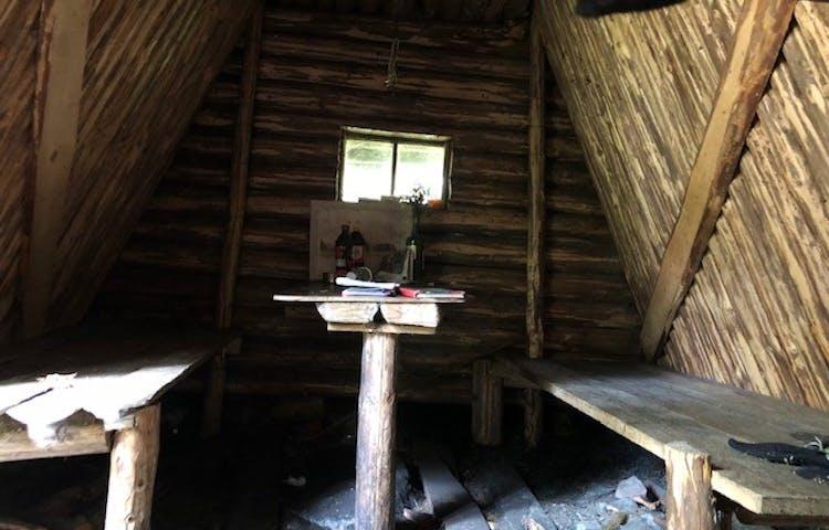Inne i Kolarkojan. Två enkla britsar längs väggarna och ett bord i mitten.