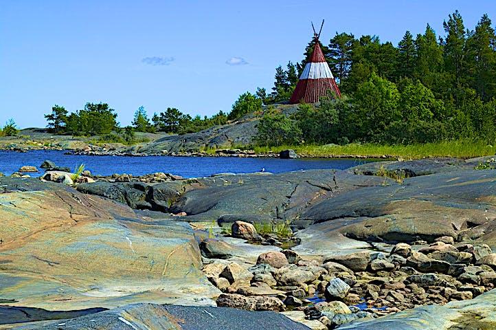 Släta ojämna klipphällar intill havet. I bakgrunden syns många träd och ett sjömärke i form av en hög kon.