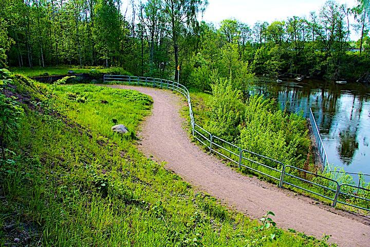 En grusad väg går intill ån med ett staket emellan.