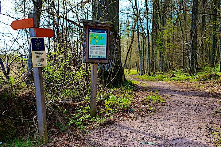 Två orange pilar på stolpe visar vägen. Informationstavla över naturreservatet.