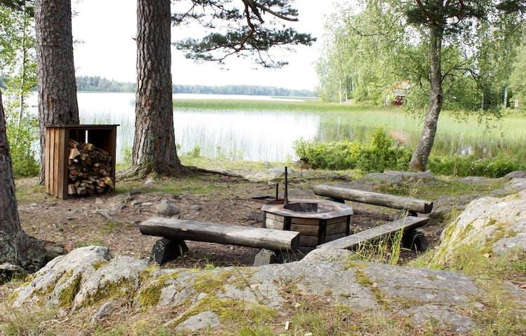 En eldstad med vedlager och tre stockbänkar står ett stenkast från vattenkanten.