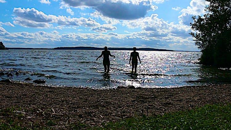 Två personer badar vid en vik.