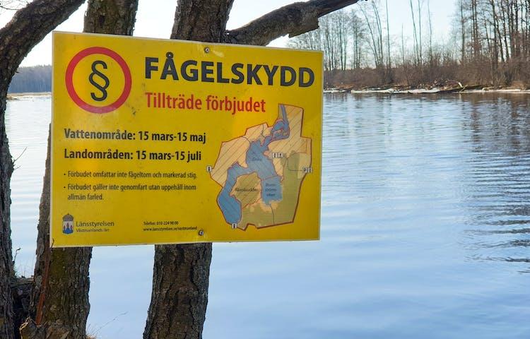 Gul skylt med områdeskarta och text fågelskydd