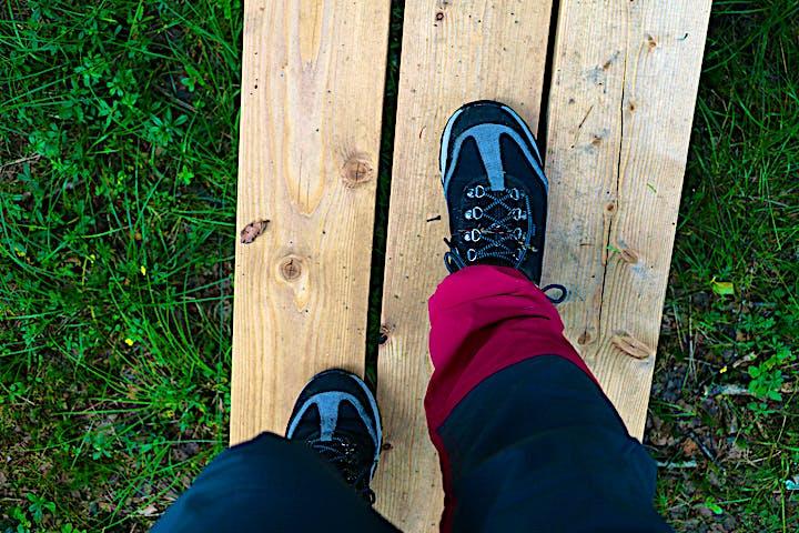 Två kängbeklädda fötter som går över en spång, fotat uppifrån.