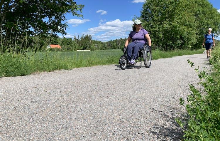 En kvinna i manuell rullstol åker på en bred grusstig som ser jämn ut.