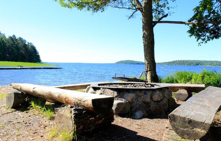 En grillplats med fyra sittbänkar runtom står på en strand vid vattnet.