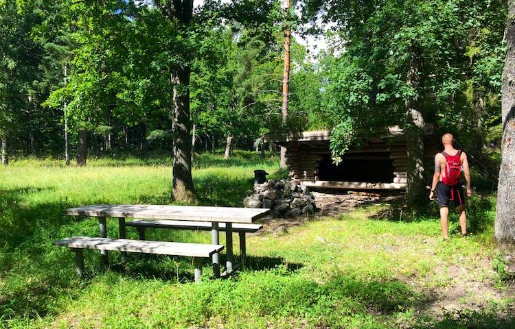 Grillplats med bord och bänkar, i bakgrunden ett vindskydd.
