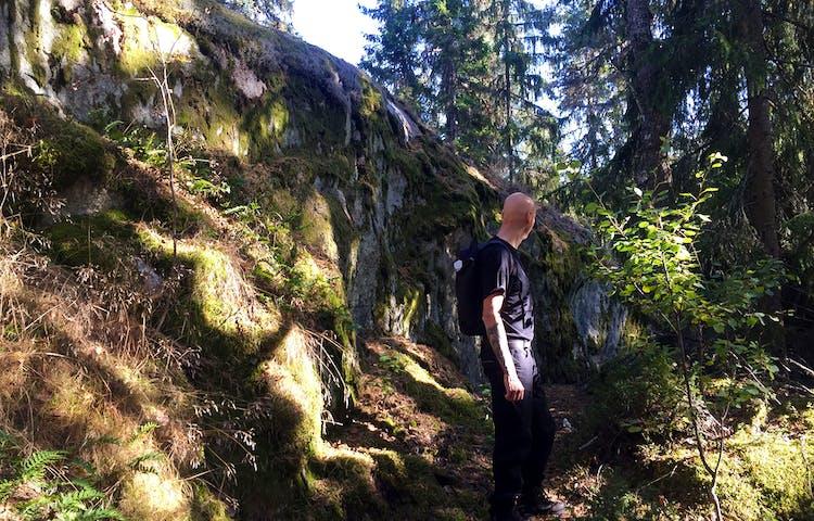 En man står bredvid en brant klippvägg som är dubbelt så hög som han är lång.