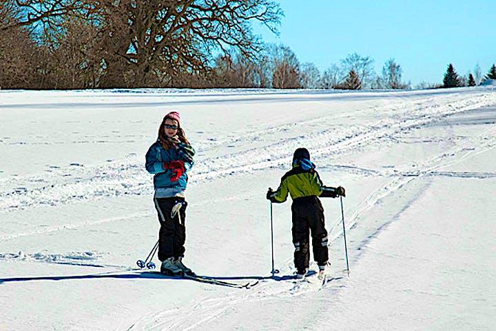 Barn åker skidor i ett öppet snölandskap kantat av gamla träd.
