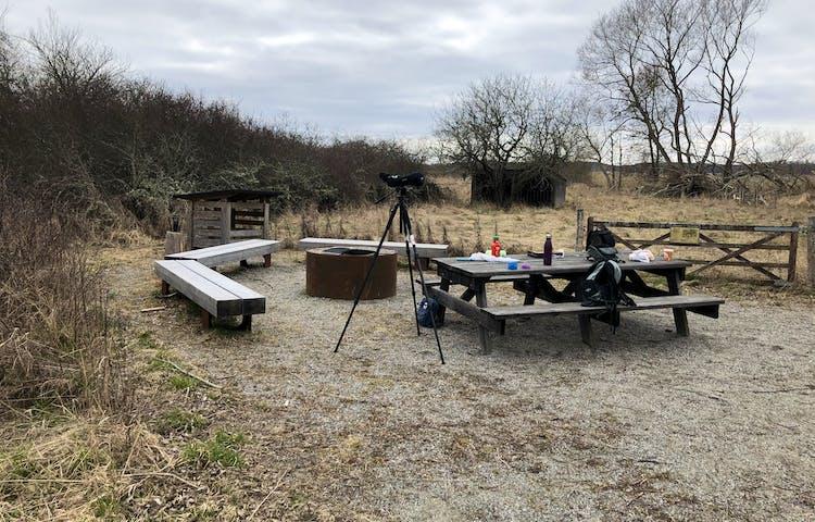 En rastplats med ett picknickbord med fika uppdukat, en rund grillplats med tre träbänkar runt omkring, ett vedskjul i bakgrunden. På bilden finns också en uppställd tubkikare.