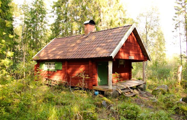 Röd stuga med fönsterluckor.