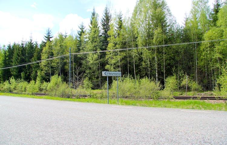 Vägskylt som visar var man ska svänga in till naturreservatet.