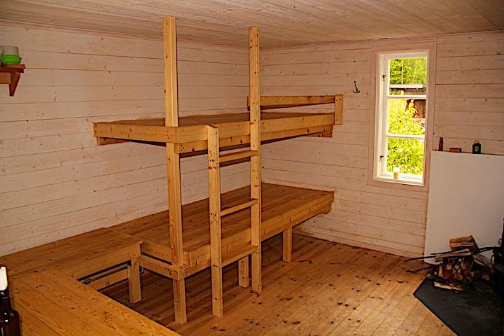 Våningssäng med stege och fallskydd på övre slafen.