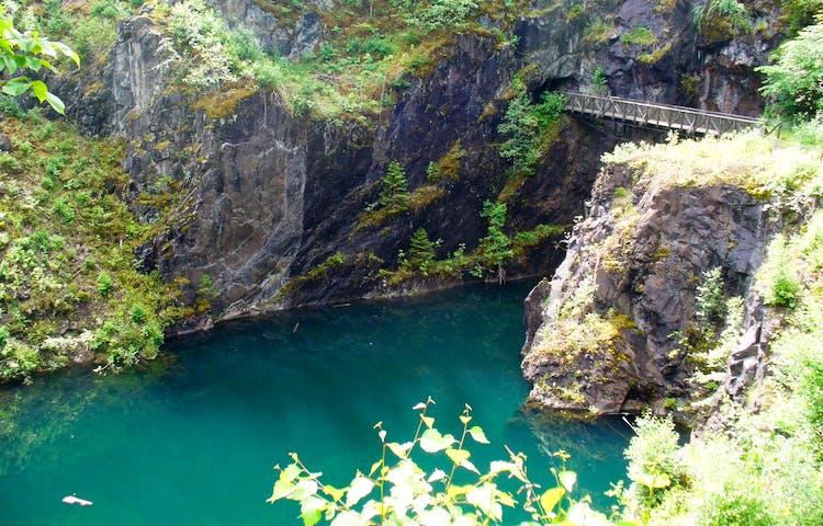 Dagbrott med turkosfärgat vatten och en bro som leder över.
