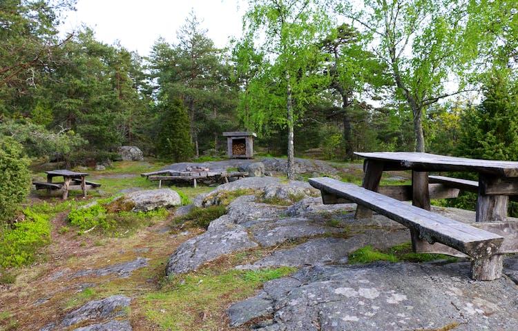 På rastplatsen finns flera bänkar med bord och en grillplats.