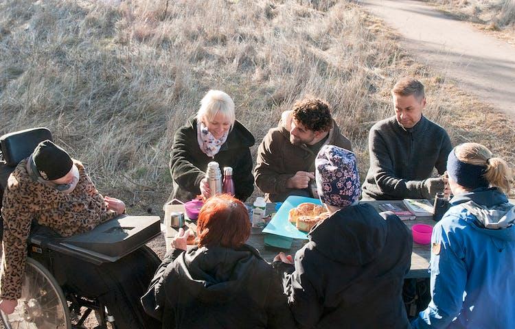Sju personer sitter och fikar runt ett bord i naturen.